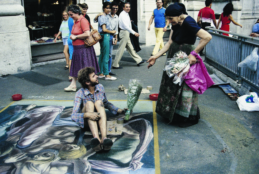 "Advice to artists. Rome's ""Flower Lady"" was a familiar sight in the 1980s. She called out advice to the street painters and reminded the public to make a drop."
