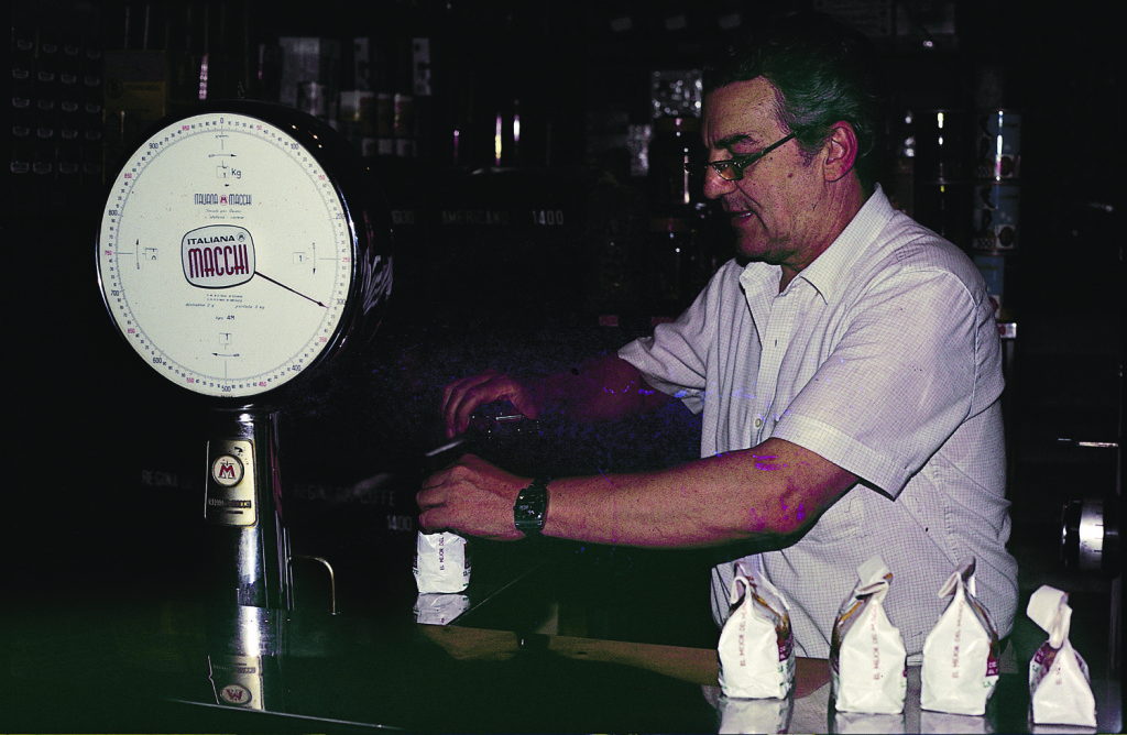 Weighing coins. The Italian lira was a bulk currency. Pound for pound, its value was roughly the same as espresso coffee or parmesan cheese. Street painters brought home many kilos of coins each day. Alfredo, the kind manager of the famous bar Tazza d'Oro, weighs and bags Wenner's coins.
